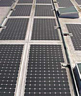 Photovoltaic solar panels are integral to a single-ply membrane roof